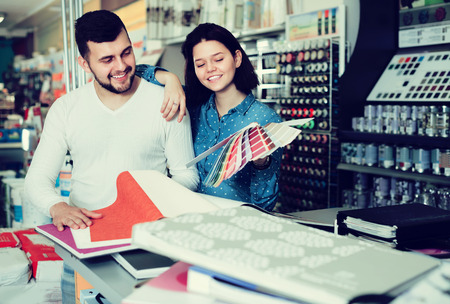 Young family couple examining color scheme in paint supplies store