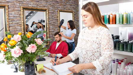 Portrait of young cheerful positive smiling woman  administrator inviting to beauty salon