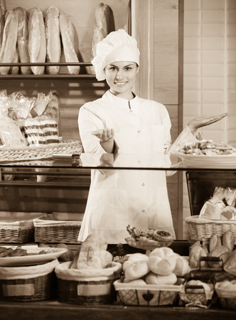 Portrait of friendly smiling cheerful young woman at bakery display with pastry