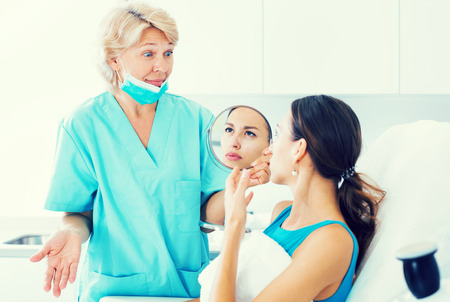 Portrait of unhappy worried woman visiting clinic of esthetic medicine