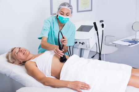 Female getting cryolipolyse treatment in cosmetic cabinet Archivio Fotografico - 110701968