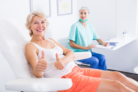 Portrait of smiling satisfied woman visiting cosmetician giving thumbs up
