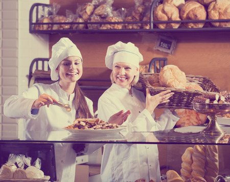Two cheerful female seller fresh pastry and loaves of bread section. Focus on the young woman