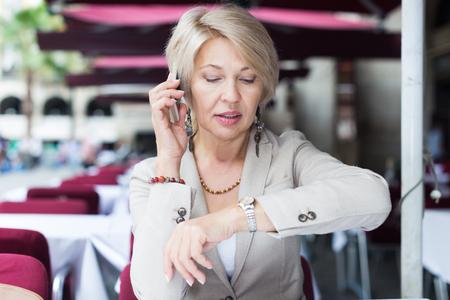 Rijpe zakenvrouw praat aan de telefoon met collega over hun ontmoeten in de tijd ontbijt in café.