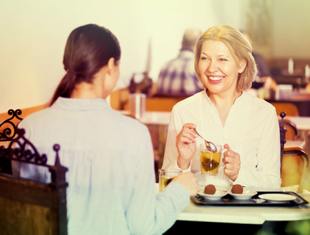 Two cheerful smiling female friends relaxing at cafe with tea and dessert Reklamní fotografie