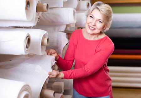 Happy woman choosing interesting fabric in textile shop
