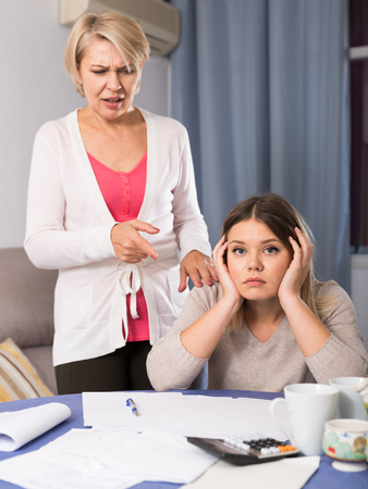 Angry mother is arguing with her daughter, who has a lot of financial problems