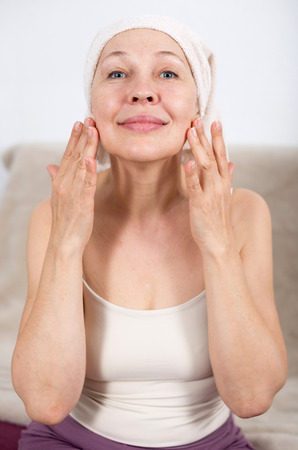 Elderly woman using face cream during beauty procedures at home Stok Fotoğraf