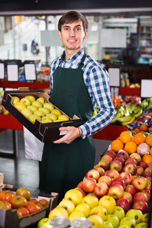 Happy adult grocery worker selling seasonal fruits in farm food store