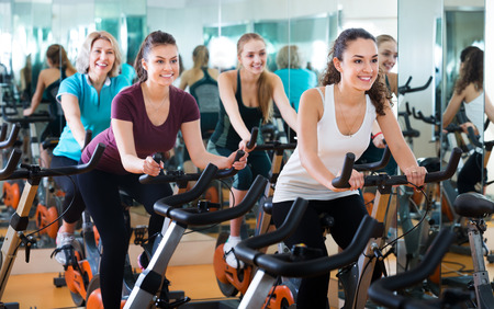 Positive females of different age training on the exercise bikes together at the modern fitness club Stock fotó