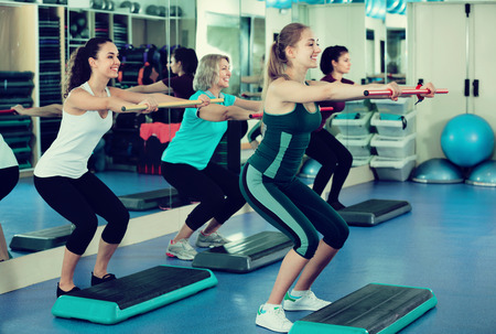 Cheerful females working out on aerobic step platform in modern gym 写真素材 - 110699794