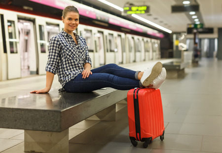 Joyful girl traveler waiting for train at metro station sitting on stone bench with legs stretched out on suitcase