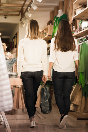 Back view of young women friends with paper bags  in  clothes shop Standard-Bild