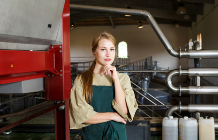 Portrait of young positive female worker in apron standing at winery