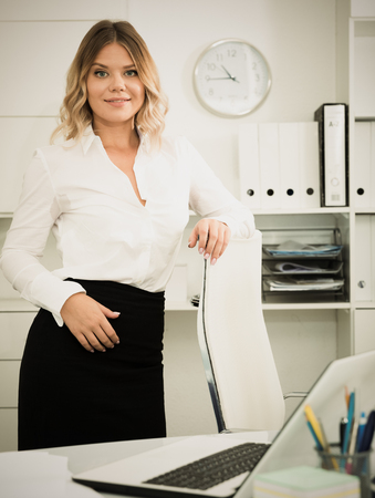 Young girl in business clothes is standing near table in office
