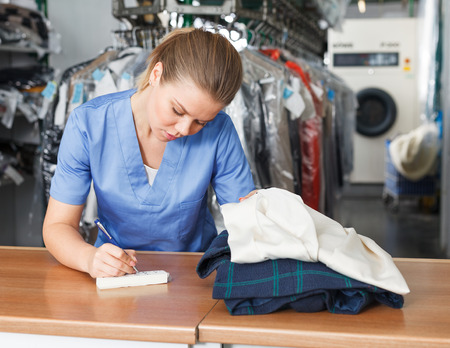 Focused girl worker of laundry writing receipt while taking clothes for dry cleaning