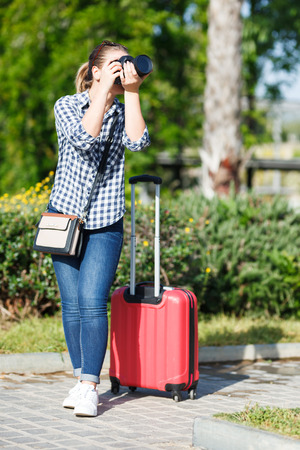 Young woman traveler strolling with luggage around city, making photo of sights