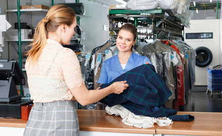 Diligent positive cheerful woman worker of laundry taking clothes for dry cleaning from female client Фото со стока