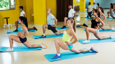 Group of glad men and women doing stretching in fitness center Imagens