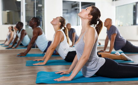 Group of active young girls and men practicing yoga asana at modern gym