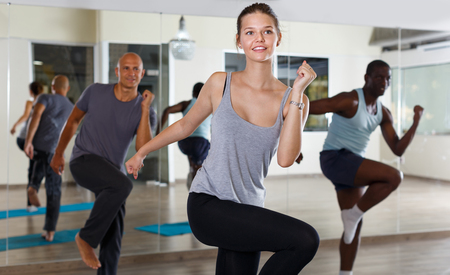 Group of happy young females and men enjoying dance techniques together in studio Banque d'images
