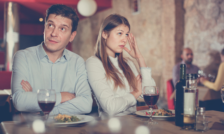 Young unhappy emotional couple quarreled in restaurant sitting at served table