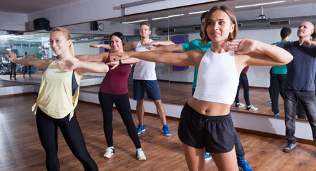 Happy beginner dancers learning zumba elements together in dancing class