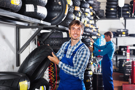 Portrait of young cheerful smiling mechanic working with bike tires in workshop Foto de archivo