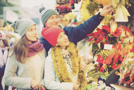 happy parents with teenage girl at counter with Poinsettia and  floral decorations at the fair Imagens