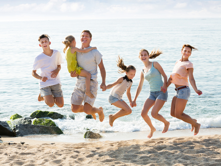 Happy parents with four children in different ages jumping on sea coast on sunny summer day