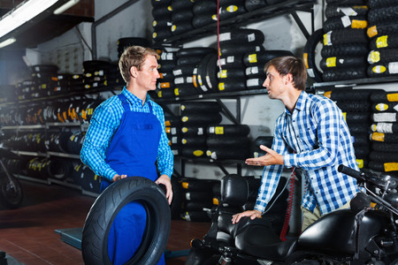 Portrait of diligent positive mechanic and customer chatting about motorbike tires at service point