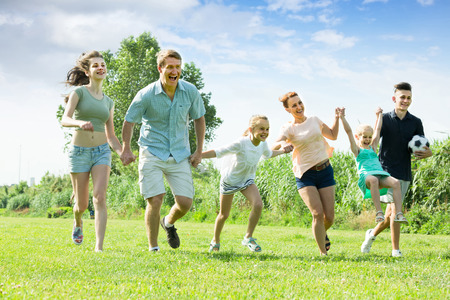 Large family happily playing and running together outdoors in summer day 免版税图像