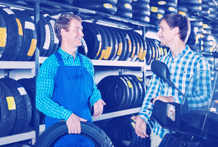 Portrait of diligent  mechanic and smiling friendly customer chatting about motorbike tires at service point
