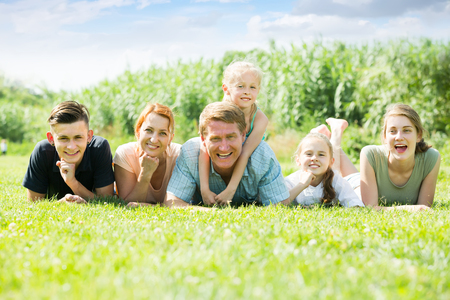 Portrait of friendly large family of six lying together on green lawn outdoors