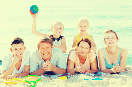 Positive young parents with four children in different ages lying on sand on sea coast in sunny weather Фото со стока