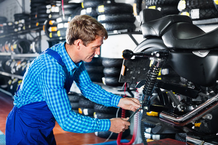 Portrait of mature diligent mechanic man working with bike in service point Stock Photo