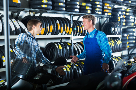 Portrait of mechanic and customer talking about motorbike in workshop