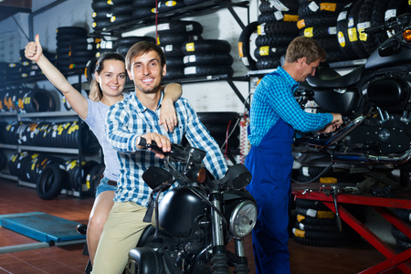 portrait of cheerful young man and woman sitting on new motorbike in workshop. Focus on man