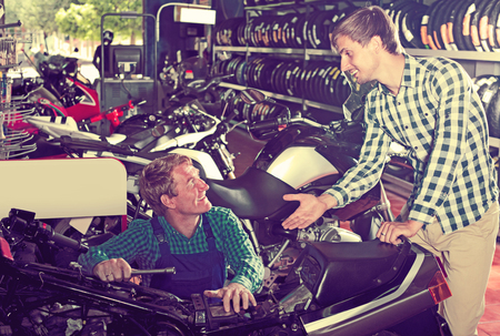Adult male technician standing with customer in shop with motorcycles