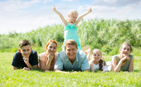 happy smiling mature couple with four different age children lying on the grass in park on summer day Stockfoto - 110887794