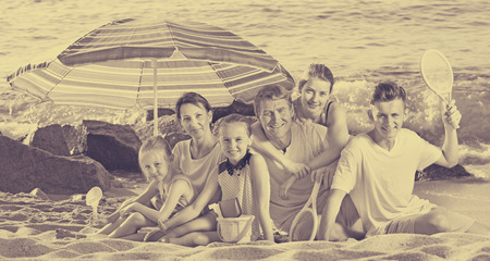 Cheerful parents with four children in different ages and beach toys sitting under the sun umbrella