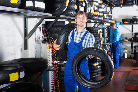 Happy working man standing with new tires for motorcycle in hands in shop Stock Photo
