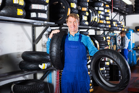 Working man standing with new auto tires for in hands in shop
