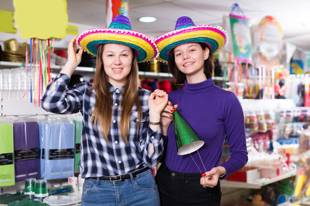 Portrait of ordinary comically dressed girls joking in festive accessories shop
