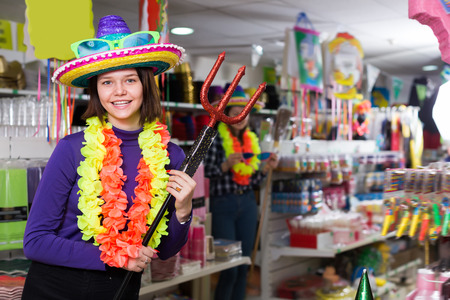 Portrait of young comically dressed girl joking in festive accessories shop