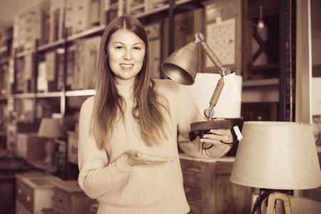 Portrait of cheerful  positive woman buyer choosing modern lamp in furniture shop