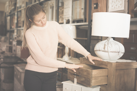 Woman buyer standing in furniture shopping room near chest of drawers Фото со стока