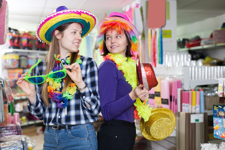 Happy women friends in comically outfits at decoration shop while preparing for party Reklamní fotografie