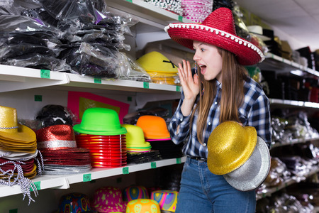 Happy attractive girl choosing funny party hats on shelves in festive accessories shop