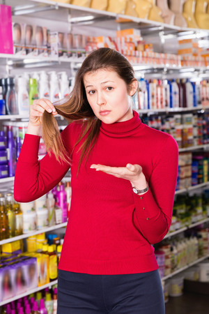 Portrait of upset unhappy angry young woman who is dissatisfied of quality her hair in the store.